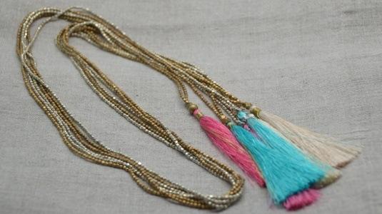 sautoirs perles argentées ou dorées avec un pompon coloré